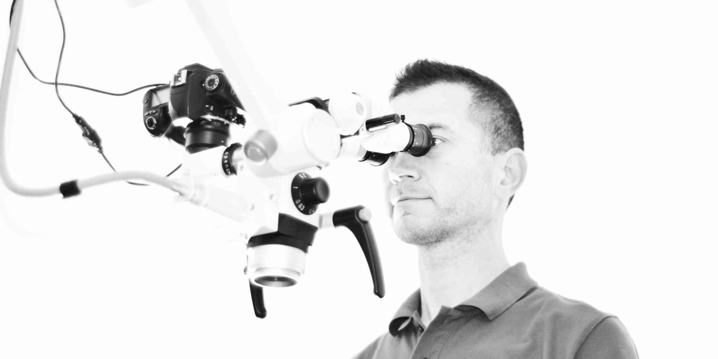 Zahnarzt Neudecker am Operationsmikroskop bei der Wurzelbehandlung
